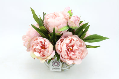 Pink artificial Peony flowers arranged in clear fishbowl vase with artificial water