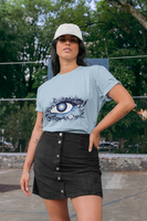 Woman wearing a Blue T-Shirt with a Floral Eye Design in Blue and White on the Front of the shirt-Personalise your own Custom T-Shirts by clicking on the link in the description