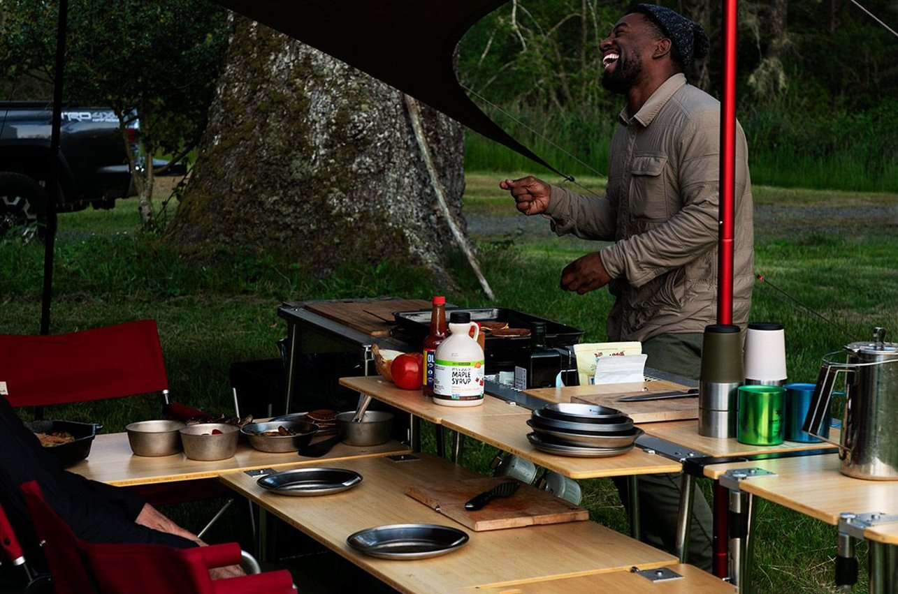 a man cooking with snow peak IGT system kitchen in a garden
