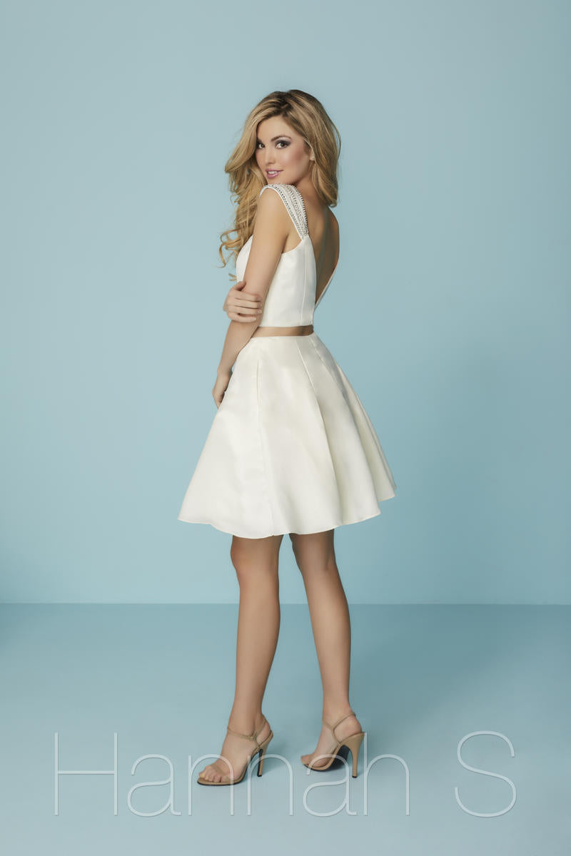 This white two-piece Hannah S 27192 short dress has a v-neckline, a-line skirt, and beaded cap-sleeves.