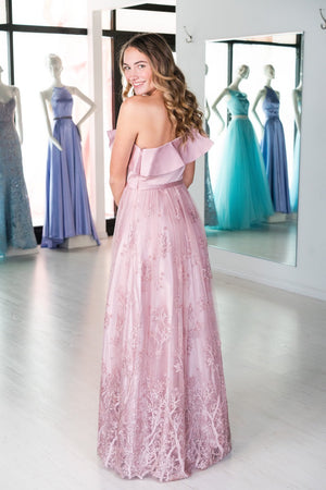 This DJ A8745 boho A-line gown in mauve features a one-shoulder ruffle neckline and a unique embroidered skirt.