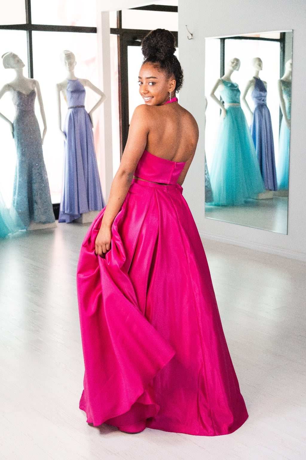 This ABU 6412 two-piece flowy gown in fuchsia features a high neck bodice, beading embellishments on the pockets, and an open back.