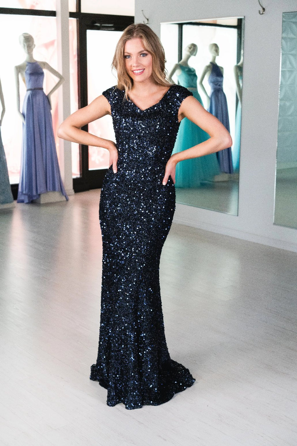 This MJS 20-502M fitted gown in navy features cap sleeves, a high back, and sequin beading throughout.
