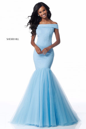 This Sherri Hill 51778 jersey gown in light blue features beading, an off-the-shoulder bodice, and a tulle mermaid skirt.