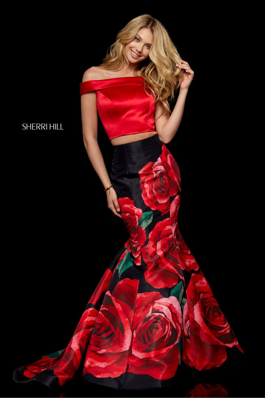 This Sherri Hill 51850 two-piece gown in red/black print features an off-the-shoulder bodice with a keyhole back and a floral mermaid skirt.