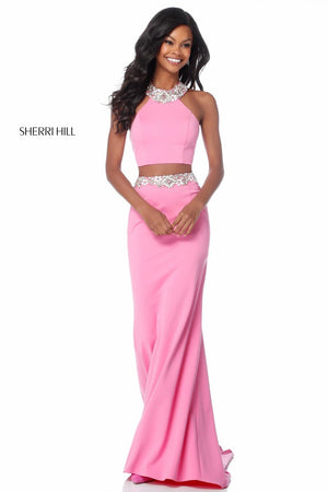 This Sherri Hill 51911 jersey two-piece gown features a high neck halter bodice and a fitted skirt with a beaded belt.