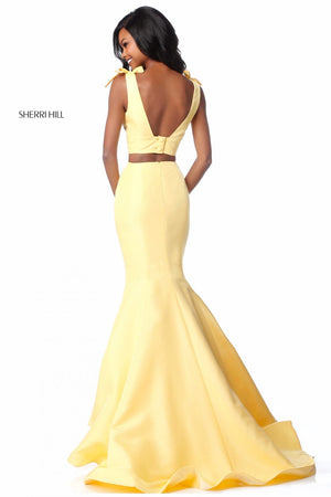 This Sherri Hill 51918 taffeta mermaid two-piece gown in yellow features bows on the shoulders and buttons on the back.