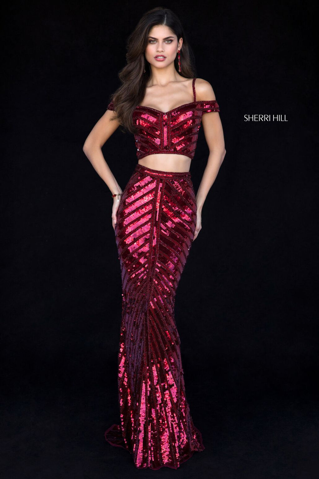 This Sherri Hill 51934 two-piece fitted gown in burgundy features sequins and off the shoulder straps.