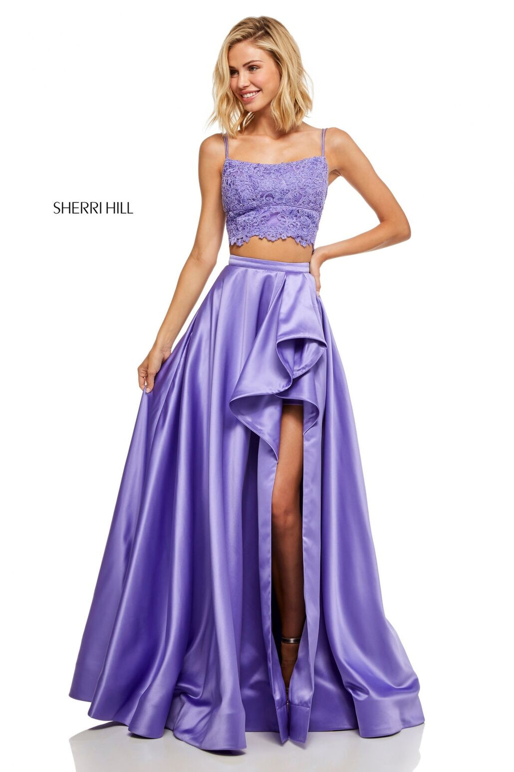 This Sherri Hill 52623 two-piece gown in lilac features a lace top and a satin skirt with a ruffle slit.