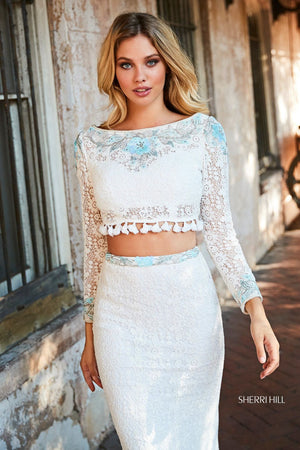 This Sherri Hill 52809 two-piece dress in ivory/aqua features crochet throughout with long sleeves and a beaded bodice.