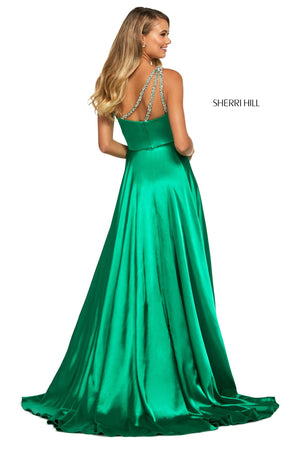 This Sherri Hill 53295 charmeuse A-line gown in emerald features a one shoulder neckline with beaded straps and a skirt slit.