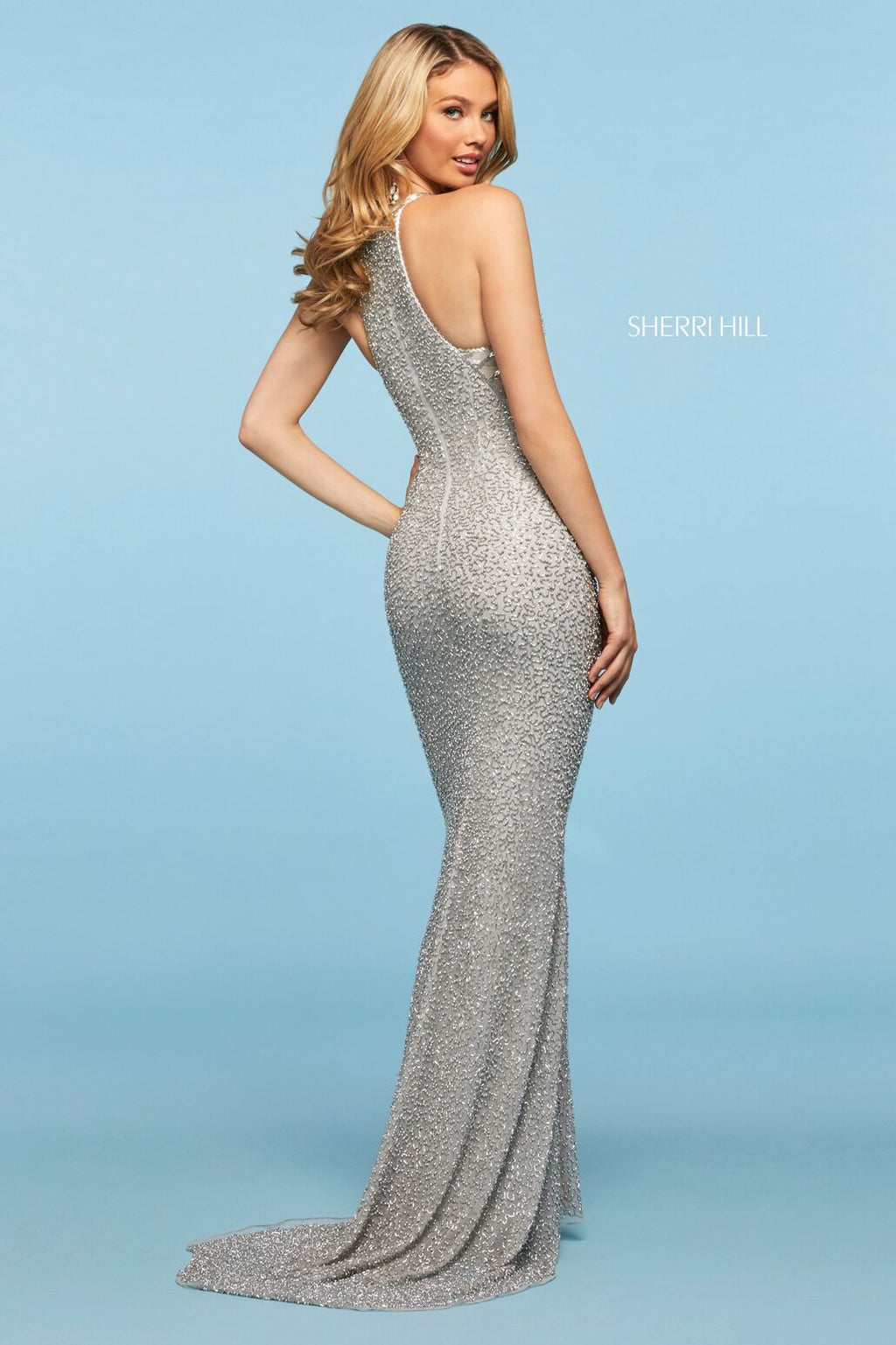 This Sherri Hill 53440 fitted gown in silver features a high cut halter style neckline and beading throughout.