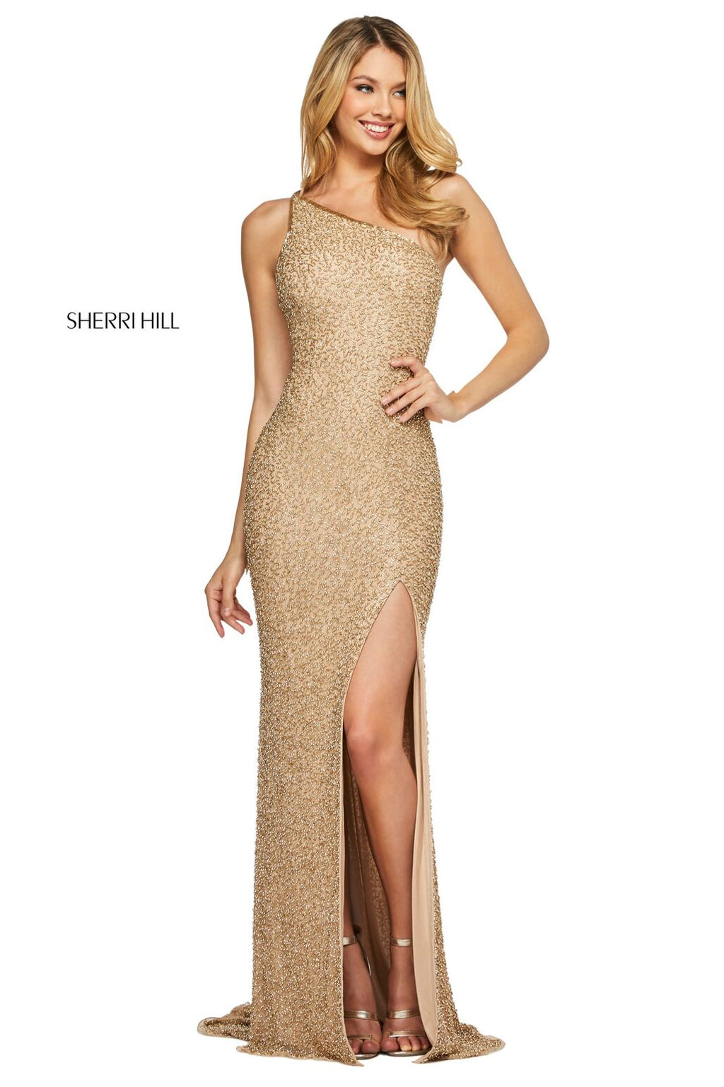 This Sherri Hill 53514 beaded column gown in gold features a one shoulder neckline and a skirt slit.