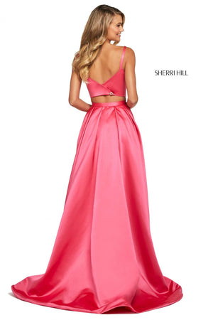 This Sherri Hill 53527 mikado two-piece gown in coral features a bateau neck bodice and a long wrap skirt with an embellished trim.