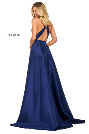 This Sherri Hill 53529 A-line satin gown in navy features a high cut halter style neckline and embellished skirt pockets.