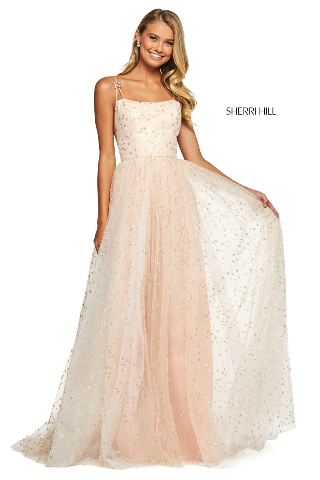 This Sherri Hill A-line gown in blush/gold features glitter, a straight neckline, and jeweled star embellishments on the spaghetti straps.