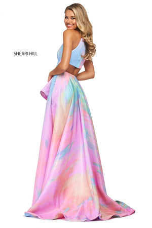 This Sherri Hill 53870 A-line dress in ivory/multi features a tie-dye print, a ruffled skirt slit, and high cut halter style neckline with a back cut out.