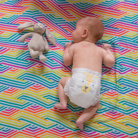 Baby having tummy time on large colourful Pattie & Co. muslin
