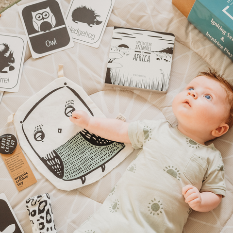 Baby lying on their back surrounded by black and white sensory toys