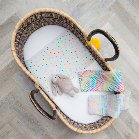 Moses basket with 3 rainbow muslin squares draped over it