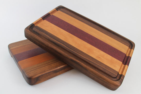 Handcrafted Wood Cutting Board - Edge Grain - Walnut, Cherry and Purpleheart. No slip bottom and easy grips. Optional juice groove.