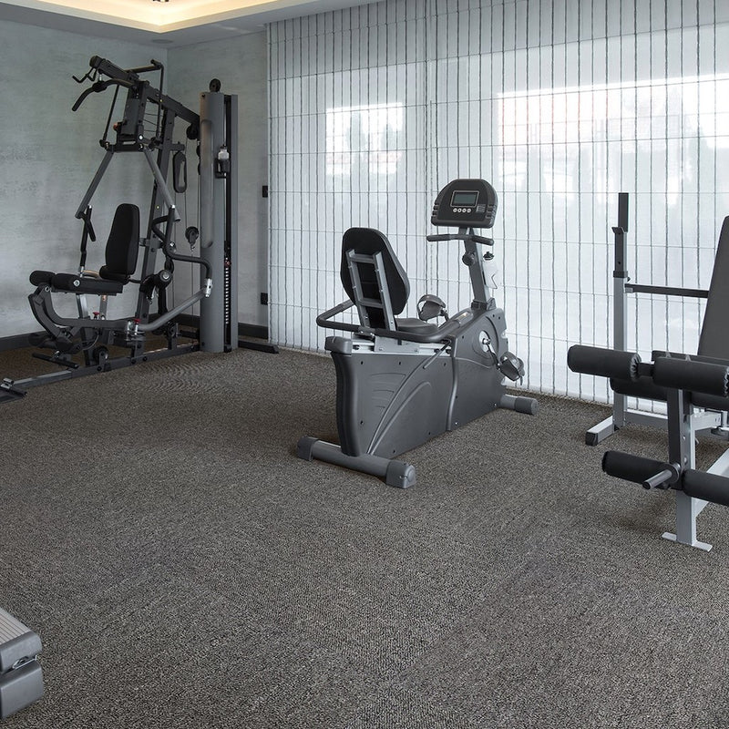 Nomad Charcoal loop carpet tiles pictured on floor of workout area