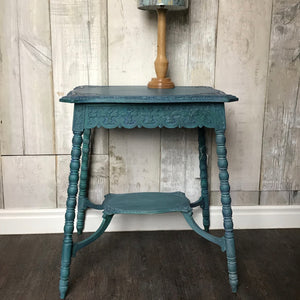 Ornately carved occasional table in shades of blue