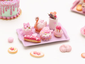 Beautiful presentation of pink miniature French pastries and treats (swan, éclair, religieuse)