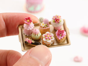 Beautiful presentation of pink miniature French pastries and treats on gold tray – Miniature Food