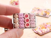 Load image into Gallery viewer, A hand for scale holding a miniature metal tray filled with handmade miniature food sweet treats including meringues in pink made from polymer clay
