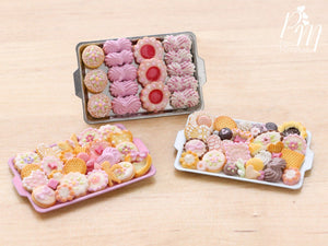 A collection of three miniature metal trays filled with handmade miniature food sweet treats including meringues and cookies made from polymer clay