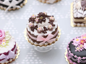 Cream Cake Decorated with Chocolate Palets, Bows, Blossoms and Macaron - Miniature Food