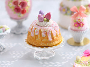 Easter Kouglof decorated with pink egg meringue nest and sparkly frosting