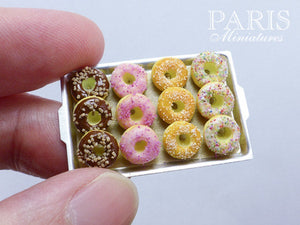 A hand holding Handmade Miniature Donuts on a metal tray to show 12th scale