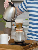 Angled shot of someone in the process of brewing coffee using a Chemex Coffeemaker 3 Cup.