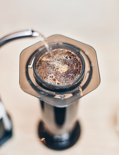 Close-up top view of the top of an Aeropress in the process of being brewed.