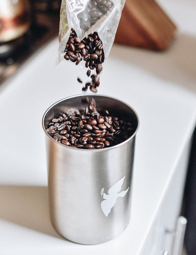 Angled top view of someone pouring coffee beans into an Airscape Coffee Canister.
