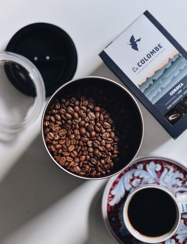 An opened Airscape Coffee Canister with coffee beans with a cup of coffee and a box of Corsica.