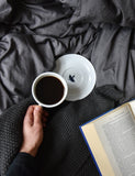 Someone in bed using a Cafe Latte Mug and Saucer to drink coffee while reading a book.