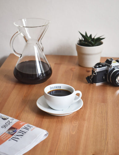 A Cafe Latte Mug & Saucer filled with coffee along with a Chemex Coffeemaker and a camera.