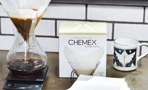 A box of Chemex Square Filters 6 Cup, a stack of Chemex filters, a Chemex Coffeemaker, and a mug.