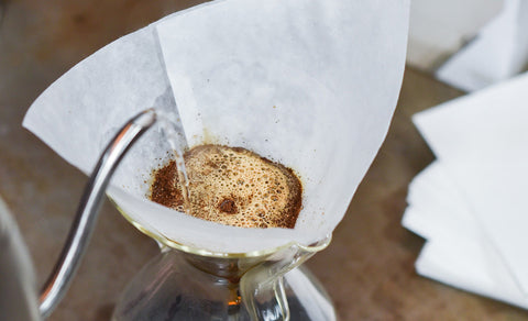 Someone pouring hot water into a Chemex Coffeemaker 6 Cup using a Chemex Square Filter 6 Cup.