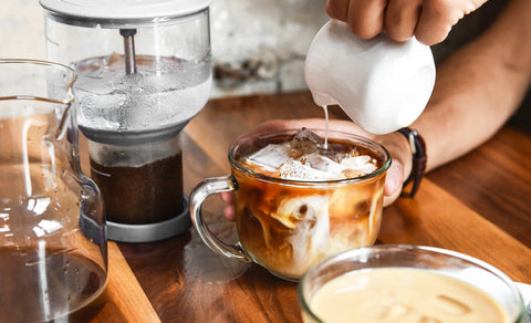 Angled shot of someone pouring milk into a cup of freshly made cold brew after using a Bruer.