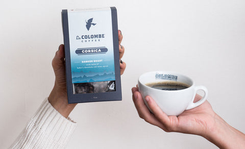 One hand holding a box of corsica coffee beans, another hand with a full cup of coffee.