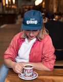 Another image of someone wearing a Red Eye - 5 Panel Hat while drinking coffee.