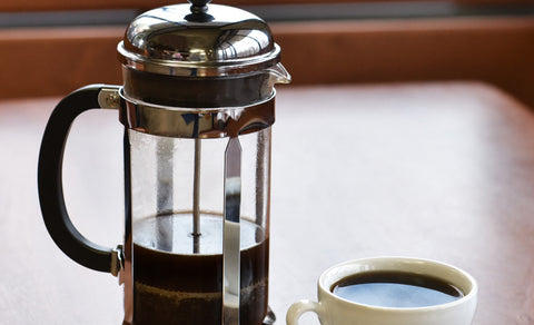 Angled shot of a Bodum Chambord French Press next to a cup of coffee.