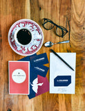 Top view of several La Colombe Gift Cards with a cup of coffee, a card, and a pair of glasses.