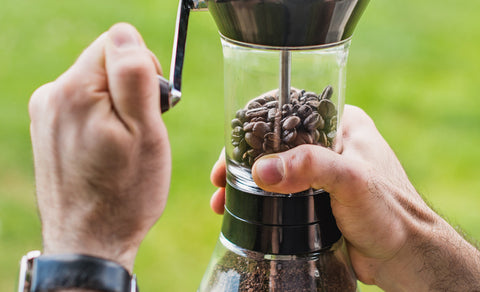 Angled shot of someone using a Handground Precision Coffee Grinder outside.