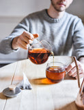 Image of someone pouring freshly brewed tea from a Hario Teapot in a mug.