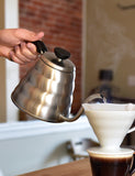 Angled shot of someone using a Hario Buono Kettle 1.2L into a Hario V60.